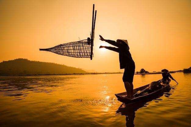 Pêcheur, sur, rivière, bateau, coucher soleil, asie, pêcheur, bambou, poisson, piège, sur, bateau, coucher soleil