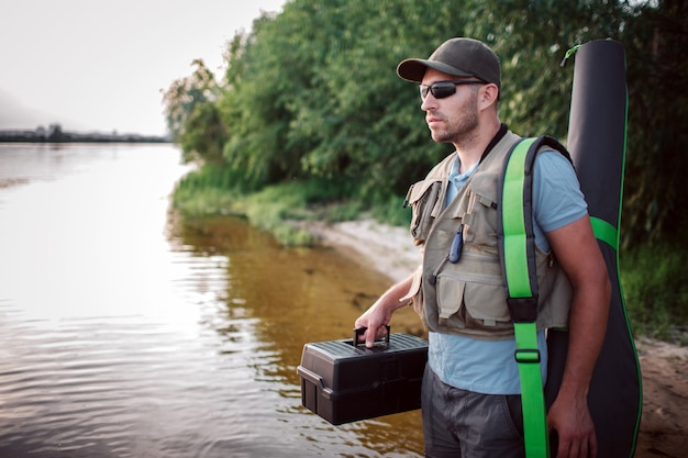 Un pêcheur sérieux se tient debout peu profond et regarde droit devant. il tient une boîte noire en plastique dans une main et couvre la tige de fli avec une autre.