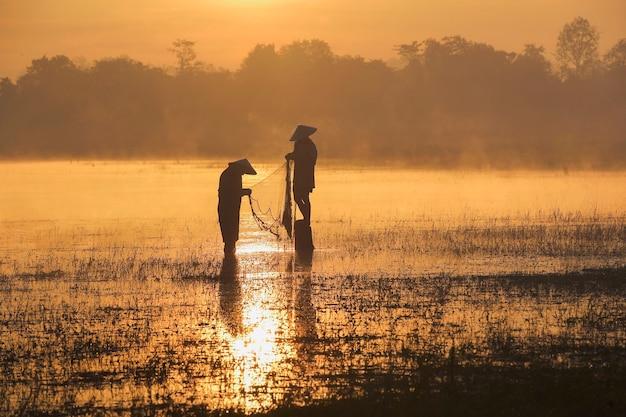 Pêcheur de silhouettes jetant des filets de pêche pendant le coucher du soleil.