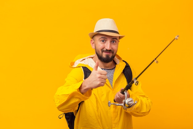 Pêcheur de smiley donnant les pouces vers le haut tout en tenant la canne à pêche