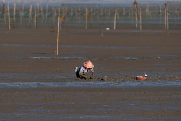Un pêcheur travaillant sur la plage noire