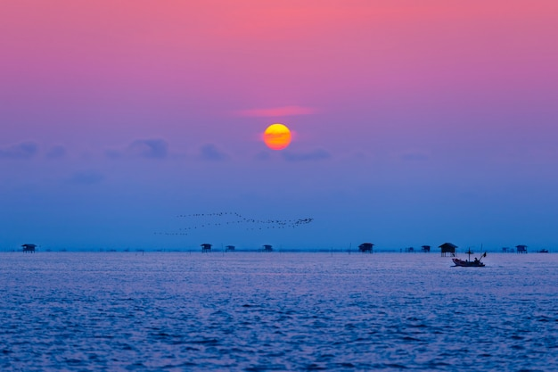 Pêcheur et village flottant dans l'océan au lever du soleil