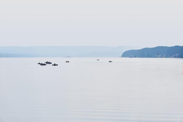 Les pêcheurs sur des bateaux pneumatiques pêchent sur une large rivière calme dans le brouillard du matin