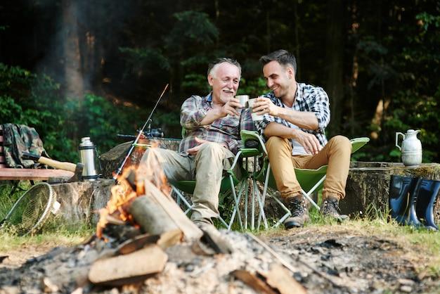 Pêcheurs buvant du café à côté d'un feu de joie