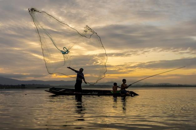 Les pêcheurs casting sortent pêcher tôt le matin avec des bateaux en bois, de vieilles lanternes et des filets. concept de vie du pêcheur.