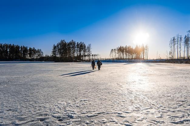 Les pêcheurs avec leurs prises vont sur la glace