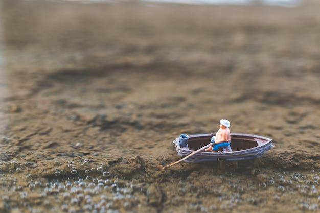 Les pêcheurs miniatures pêchent en bateau