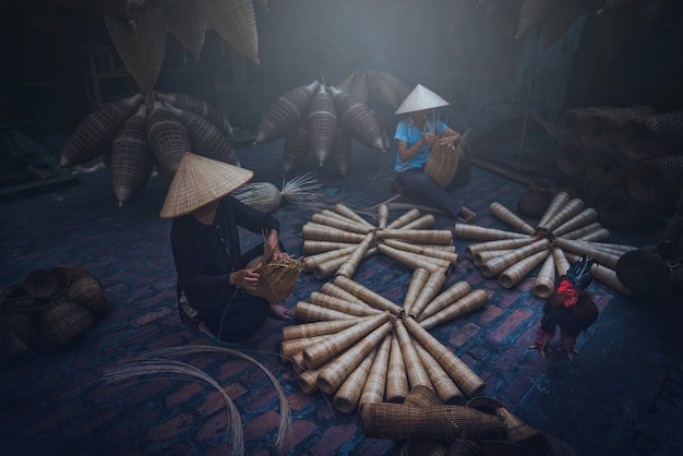 Des pêcheurs vietnamiens font de la vannerie pour l'équipement de pêche dans le village de thu sy
