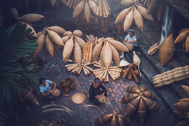 Les pêcheurs vietnamiens font de la vannerie pour l'équipement de pêche le matin dans le village de thu sy, au vietnam.