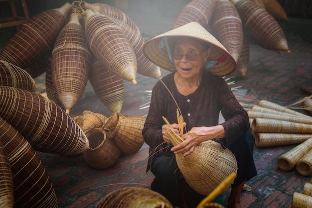 Des pêcheurs vietnamiens font de la vannerie pour l'équipement de pêche le matin dans le village de thu sy