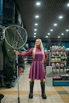 Une pêcheuse en bottes de caoutchouc tient un filet dans un magasin de pêche, des crochets et des babioles