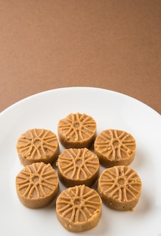 Pédha sucré indien ou pera, nourriture du festival, servi sur une assiette en céramique blanche, isolé sur fond coloré