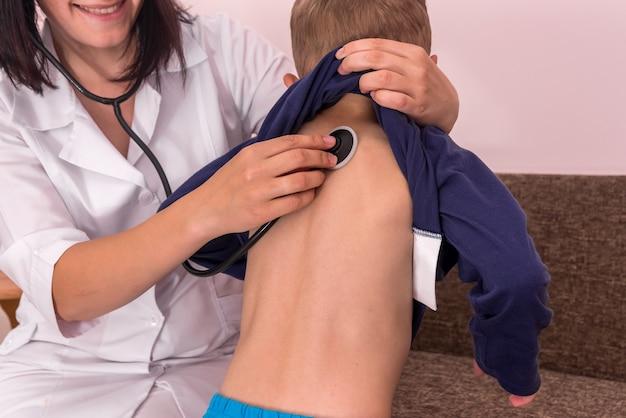 Pédiatre écoutant la respiration du garçon avec un stéthoscope sur le dos