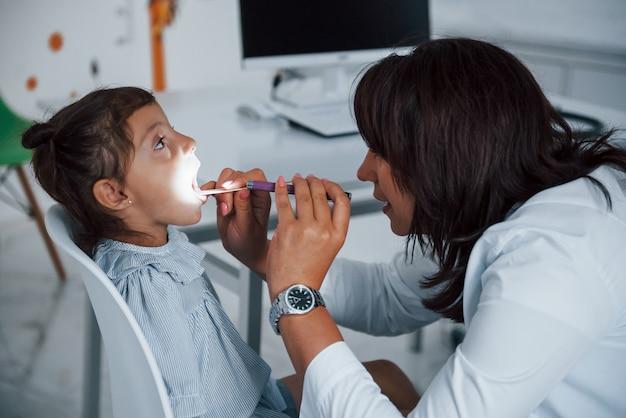 Une pédiatre expérimentée travaille avec une petite fille à la clinique.