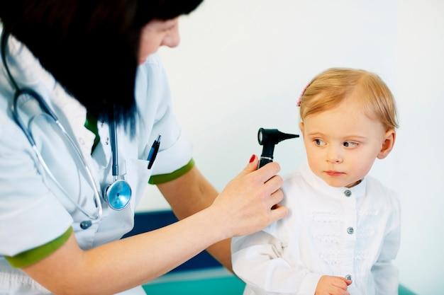 Pédiatre faisant un examen de l'oreille de bébé fille