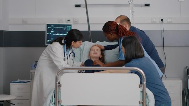 Pédiatre femme médecin tenant un petit enfant malade surveillant les symptômes de la maladie
