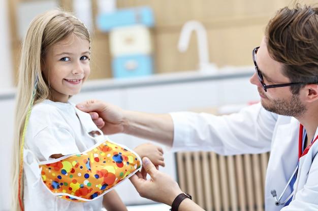 Pédiatre masculin vérifiant le bandage du bras cassé de la petite fille