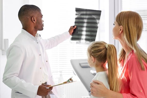 Pédiatre de sexe masculin noir expliquant et montrant la radiographie de la patte pour l'enfant malade et la mère au bureau de l'hôpital, médecin traitant les patients. se concentrer sur les gens