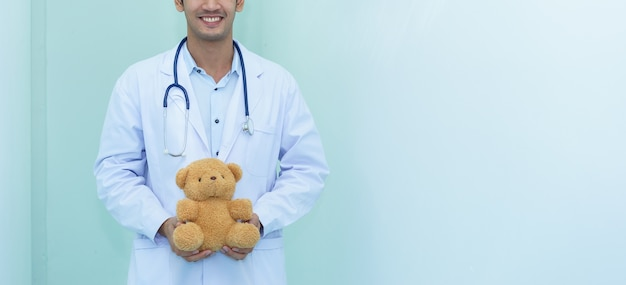 Le pédiatre tient un ours en peluche.