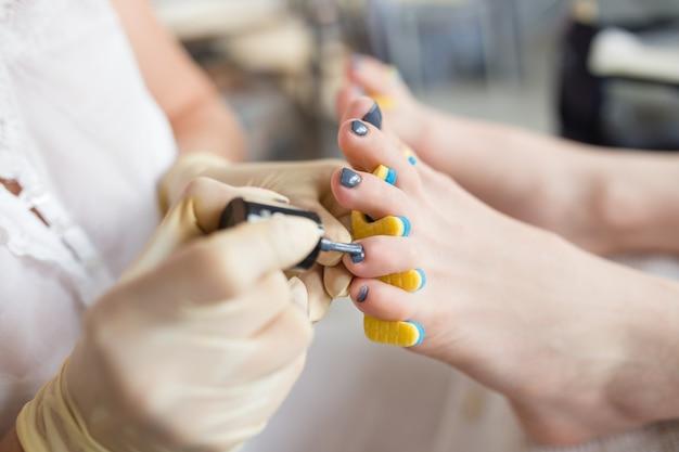 Pédicure appliquant le vernis à ongles