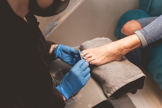 Pédicure lime les ongles avec une lime à ongles pour une application ultérieure de vernis