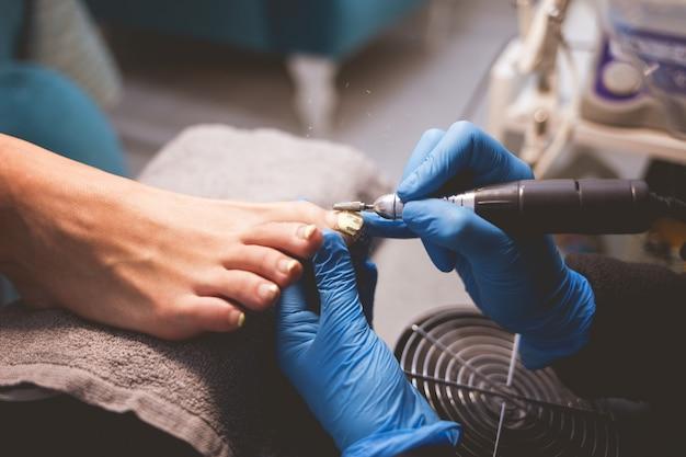 Le pédicure maître polit les ongles avant d'appliquer le vernis