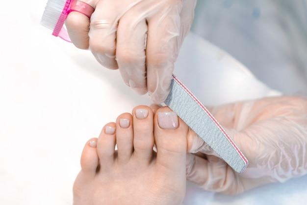 Pédicure médicale avec une lime à ongles. procédure de peeling des pieds dans le spa à l'aide d'un appareil spécial. clinique de podologie podologie.