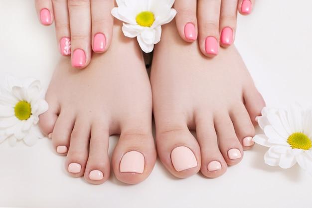 Pédicure nue et manucure pour le printemps. mains et pieds de femme sur fond blanc agrandi. résultat de la procédure du salon spa