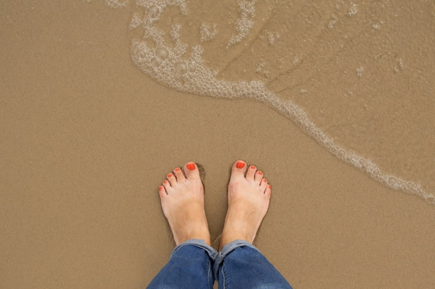 Pédicure ongles orange pieds de femme sur la plage de sable en été