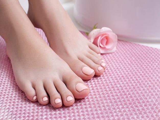 Pédicure rose parfaite sur les pieds. pieds féminins sur fond rose vue latérale avec espace libre. résultat de la procédure du salon spa