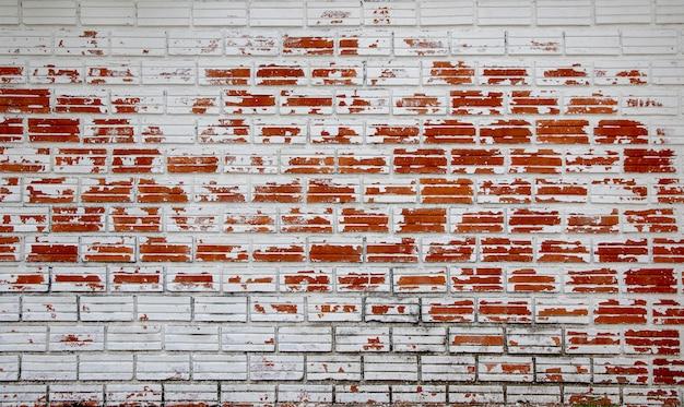 Peeling blanc peint comme vieux mur de briques rouges.