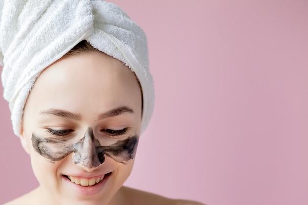 Peeling cosmétique de beauté. gros plan belle jeune femme avec un masque noir sur la peau