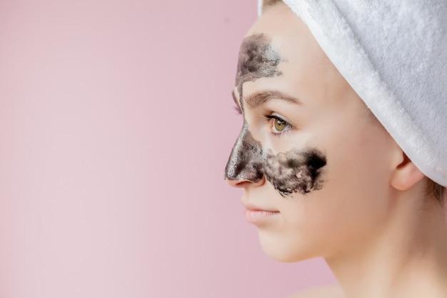 Peeling cosmétique de beauté. gros plan belle jeune femme avec masque noir peel off sur la peau.