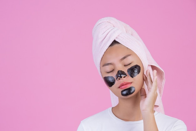 Peeling cosmétique beauté. jeune femme avec un masque pelable noir sur la peau, produit de peeling cosmétique pour le soin de la peau sur le visage, de couleur rose.