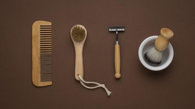 Peigne en bois, masseur en bois et accessoires de rasage sur fond marron. mise à plat.