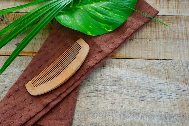 Peigne en bois avec tissu brun sur la table en bois et feuilles vertes