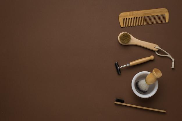 Peigne, masseur, brosse à dents et accessoires de rasage sur fond marron. mise à plat.