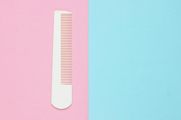 Peigne en plastique blanc sur pastel rose bleu. soins capillaires, concept de beauté. vue de dessus
