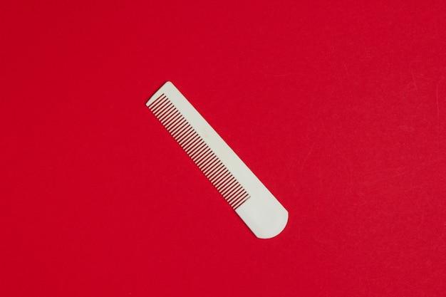 Peigne en plastique blanc sur rouge. soins capillaires, concept de beauté. vue de dessus