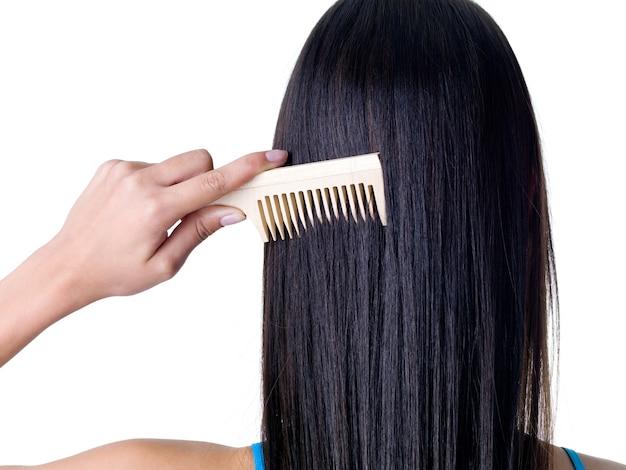 Peigner les cheveux féminins longs et droits en bonne santé - gros plan