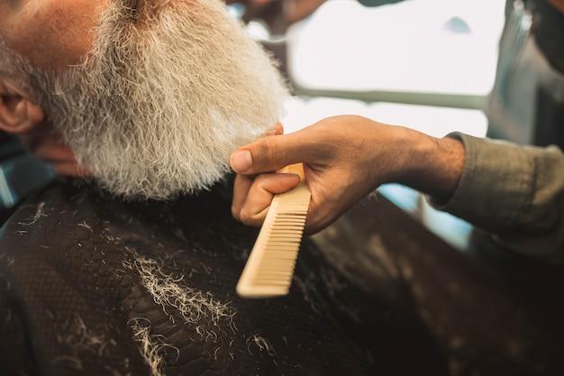 Peigner les cheveux gris du client senior dans le salon de coiffure