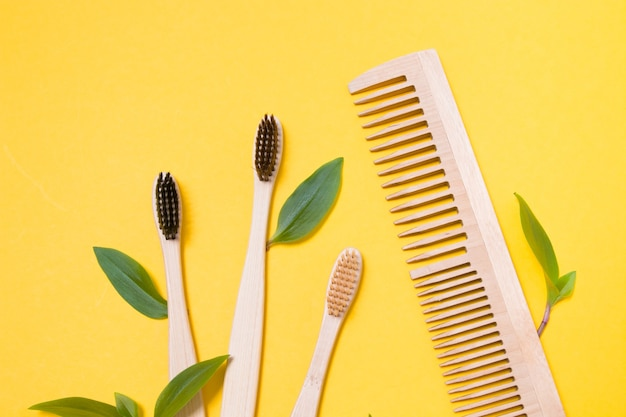 Peignes en bois et brosses à dents en bambou sur fond jaune