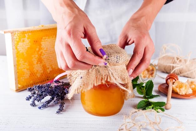 Des peignes à miel et un bocal avec des feuilles de menthe fraîche au miel et de la lavande sur une table en bois blanche