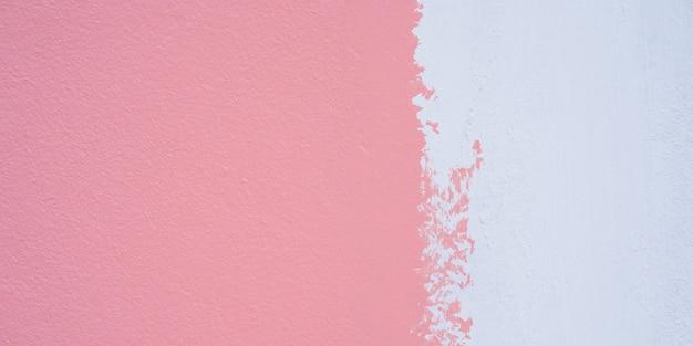 Peignez un apprêt blanc et appliquez du rose sur le mur de ciment. fond de texture de mur de ciment blanc et rose.