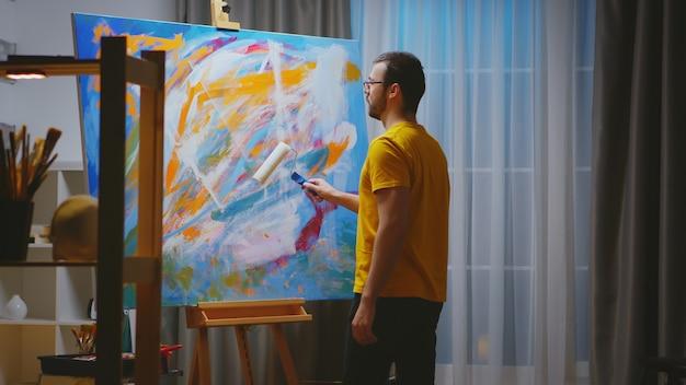 Peintre abstrait en studio d'art utilisant un rouleau pour chef-d'œuvre sur une grande toile.