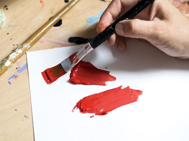 Peintre à angle élevé avec de la peinture rouge sur gros plan brosse