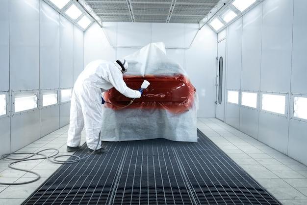 Peintre appliquant une nouvelle couche de peinture métallique fraîche sur l'automobile dans la chambre de peinture.