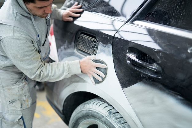 Peintre automobile préparant la voiture pour la peinture en atelier