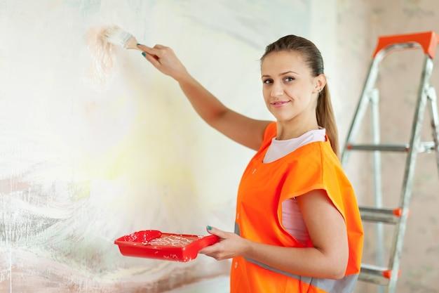 Peintre en bâtiment peint le mur avec la brosse