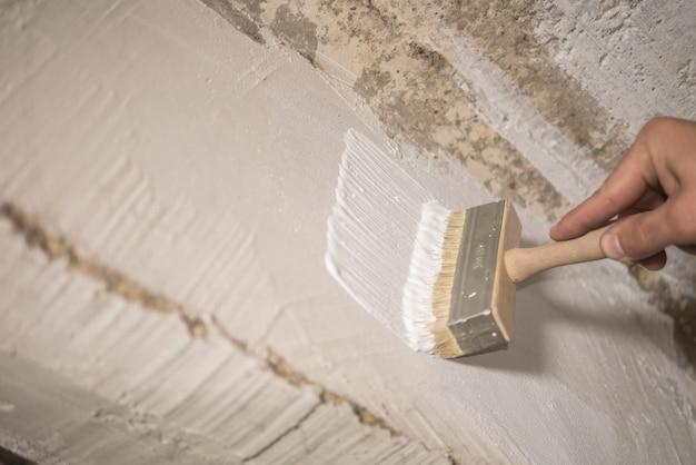 Peintre en bâtiment peint le mur avec de la peinture blanche